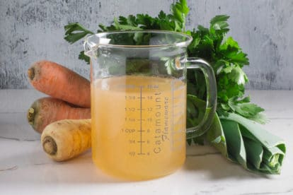 A glass measuring container filled with homemade Low FODMAP vegetable broth, in front of fresh carrots, parsnips, parsley and leeks.