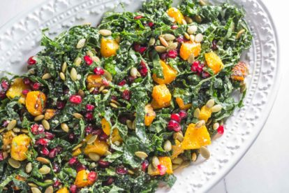 kale salad with butternut squash and pomegranate on serving platter for the table