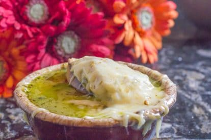 French onion soup in a brown bowl with melted cheese and red and orange flowers in the background