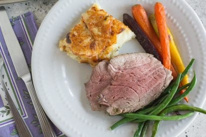 sliced leg of lamb on a plate with roasted carrots and steamed green beans