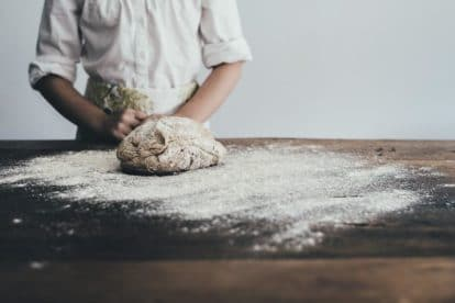 Female baker working with heavily floured dough on a wooden surface