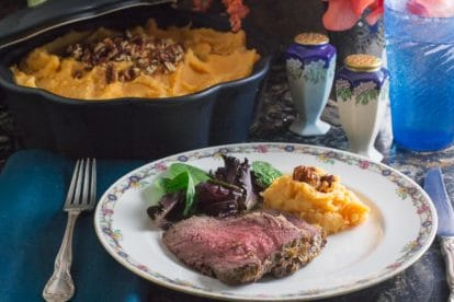 plated low FODMAP horseradish crusted roast beef with casserole of mashed sweet potatoes in backrgound