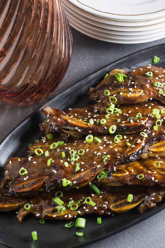 vertical image of low FODMAP Korean BBQ Short Ribs with scallions and sesame seeds on dark background
