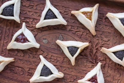 closeup of low FODMAP gluten-free Hamantaschen on wooden tray with poppy seed, strawberry and orange marmalade fillings