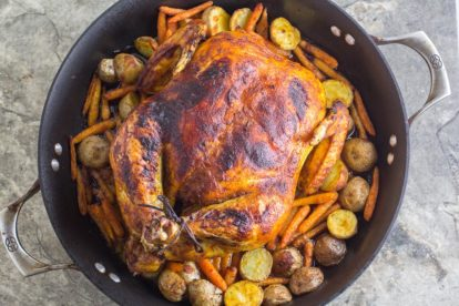 overhead image of whole roasted curry chicken with potatoes and carrots in a roasting pan against a stone backdrop