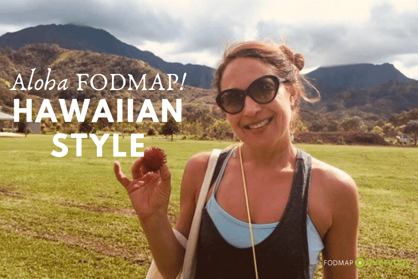 A young woman holding a small fruit while standing in front of a Hawaiian mountain.