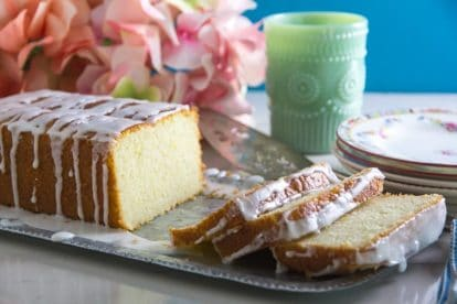 Glazed Low FODMAP Lemon Loaf on tin tray with plates in background