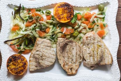 P Grilled Swordfish with Grilled Orange, Fennel and Green Olive Salad on a rectangular white platter
