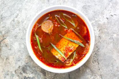 low FODMAP Kimchi and Tofu Stew in white bowl on gray stone surface