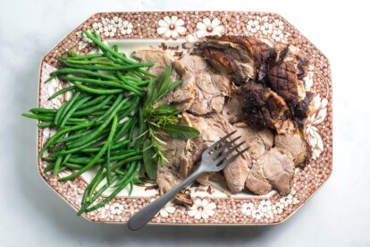 Low FODMAP Porchetta Pork Roast, sliced, with green beans on a brown and white platter with meat fork
