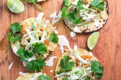closeup image Low FOMAP Shrimp Tacos with Lime Crema on wooden board; wedges of lime alongside