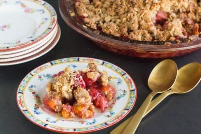 horizontal image of low FODMAP strawberry peach crisp on a decorative plate and in pie plate in background