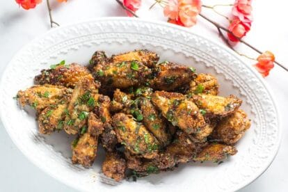 Low FODMAP Pok Pok Chicken Wings on oval white plate with coral colored flowers in background