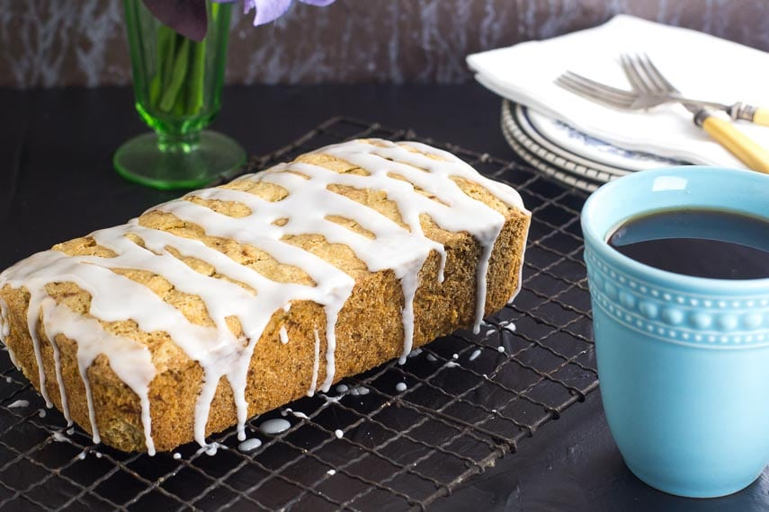 Low FODMAP lemon Zucchini loaf with drizzled glaze on top on a cooling rack; dark surface and an aqua coffee mug