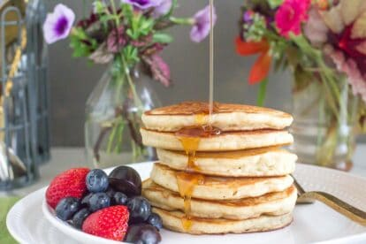 a perfect stack of low FODMAP FLUFFY Pancakes on a white plate, syrup pouring over top; fruit salad on the side