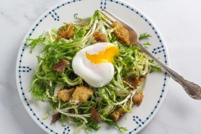 frisée salad with poached egg (broken open) on white plate with blue border