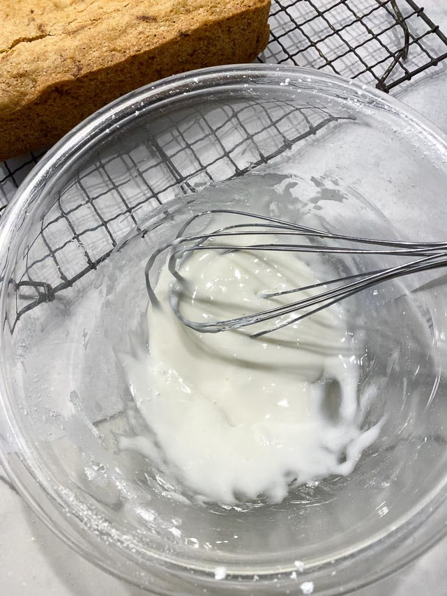 lemon glaze for quick bread being mixed in glass bowl with whisk