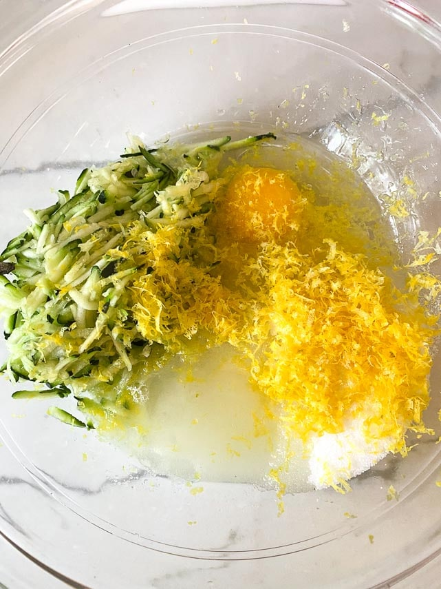 wet ingredients for lemon zucchini bread in glass bowl showing a lot of finely grated lemon zest