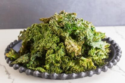 Roasted kale chips piled up on black plate, white surface, dark background