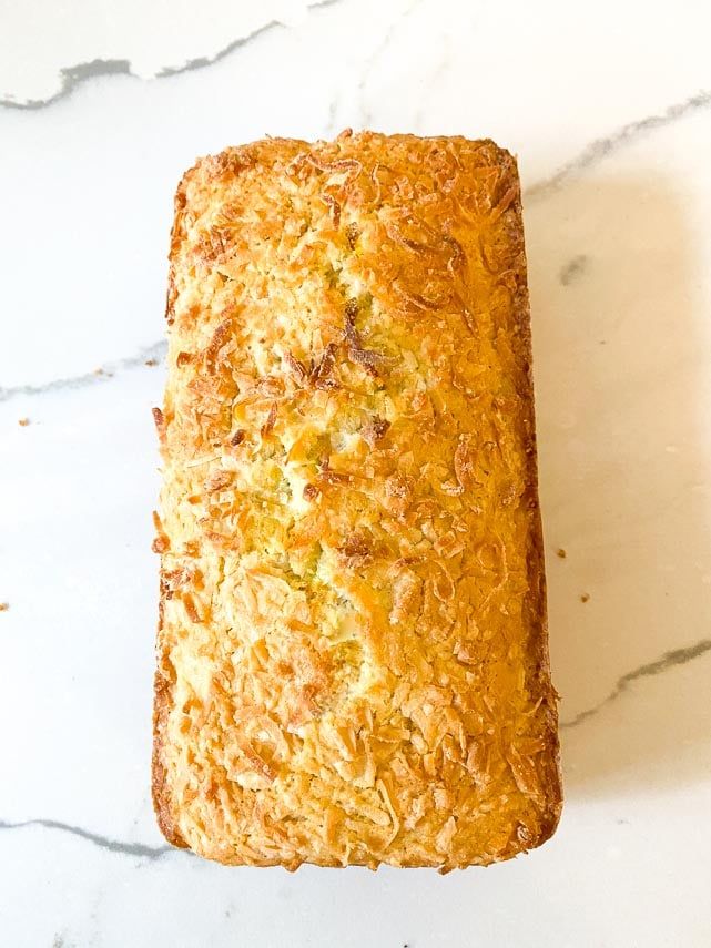 baked loaf of coconut lime bread, unmolded from pan on white marble surface