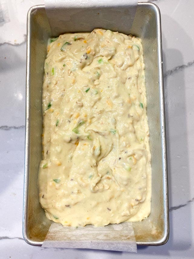 batter for beer bread scraped into loaf pan, ready to bake