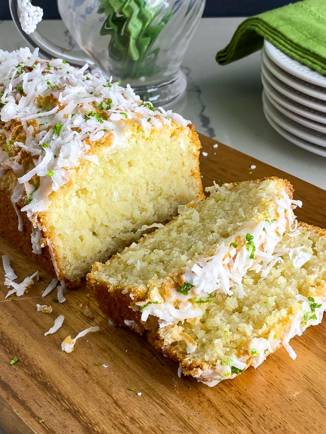 coconut lime bread on a wooden board with whole loaf in background and slices near the front of the board