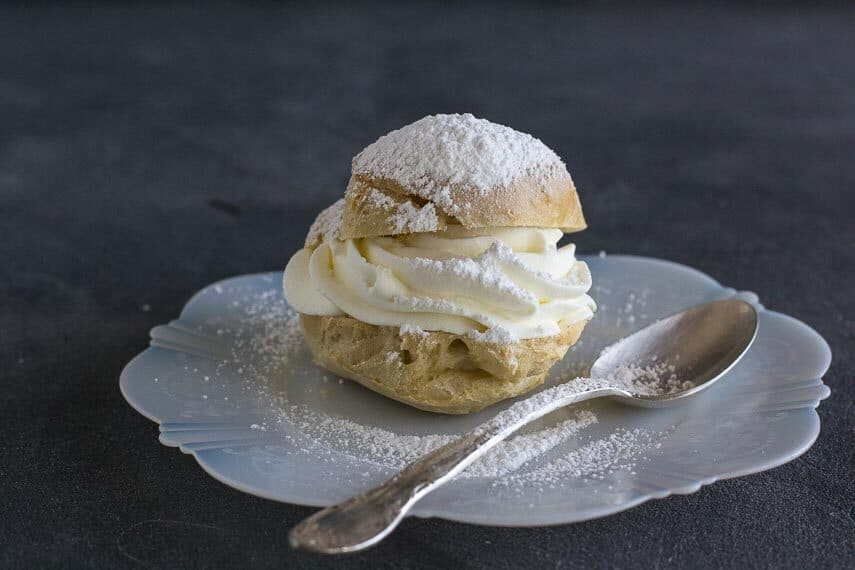 cream puff on white plate with spoon; dark background