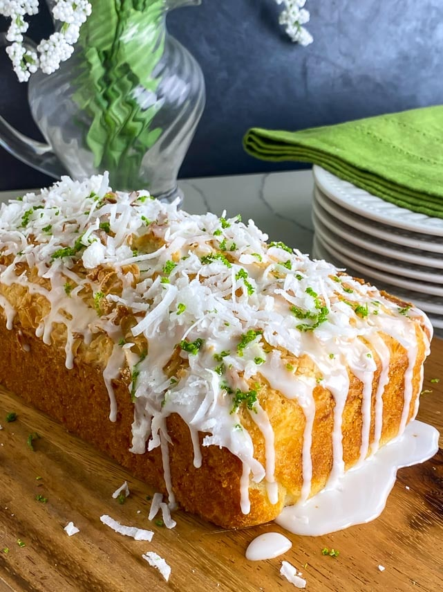 low angle image of coconut lime bread on a wooden board with glaze dripping down the sides