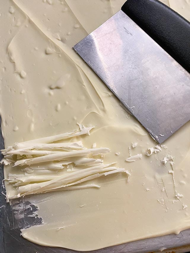 melted white chocolate spread onto back of sheet pan and allowed to firm up; using metal bench scraper to make white chocolate curls and shards