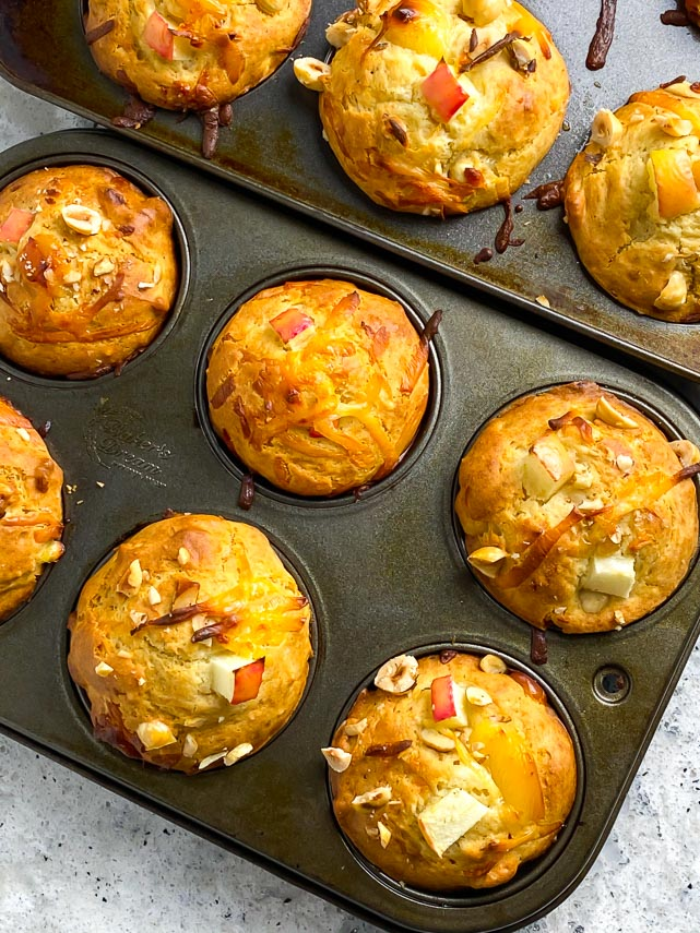 muffins tins, on the diagonal, holding smoked gouda apple muffins with hazelnuts