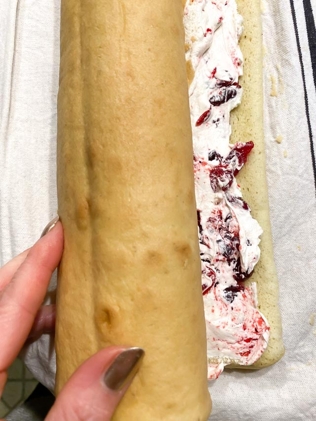 rolling up jellyroll cake with buttercream and cranberry filling