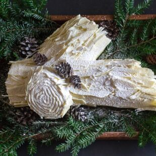 white chocolate buche de noel on wooden board with pine boughs