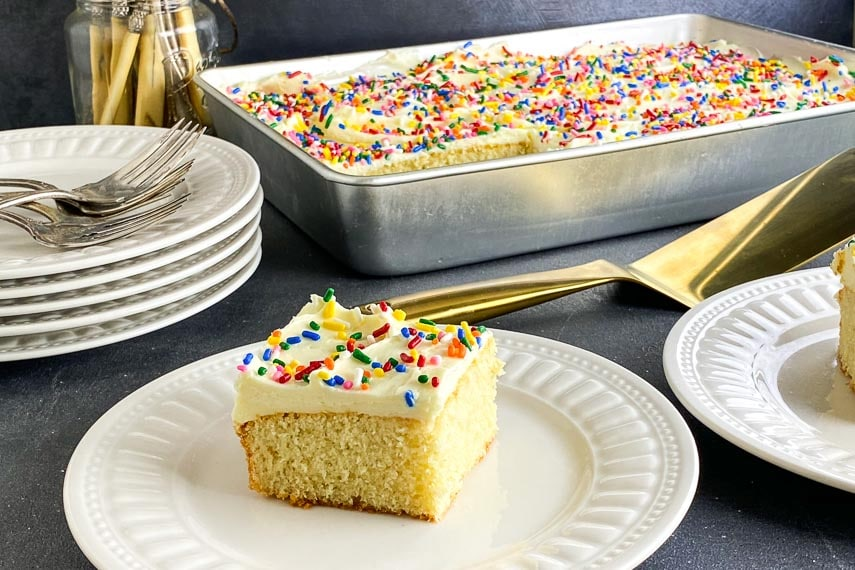 Close shot of yellow cake on white plate with vanilla frosting and rainbow sprinkles.
