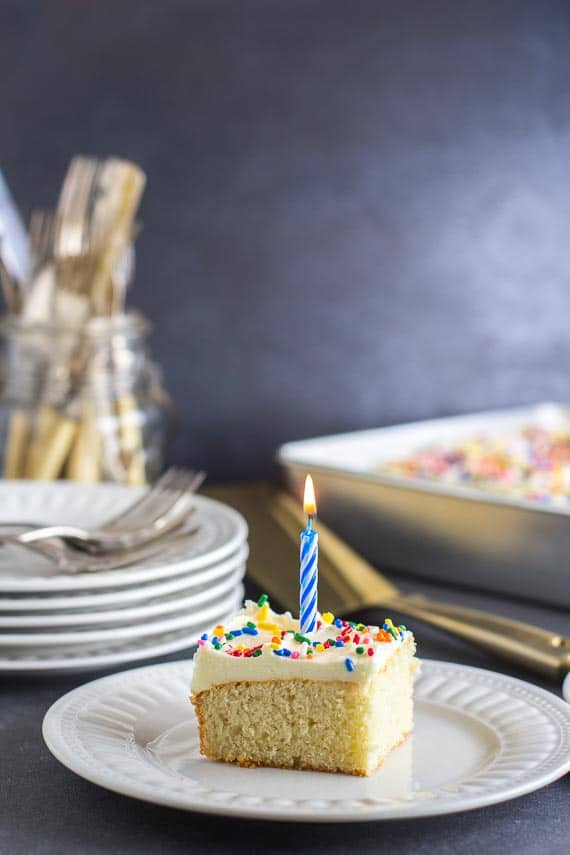 yellow cake square with vanilla frosting, rainbow sprinkles and candle on white plate